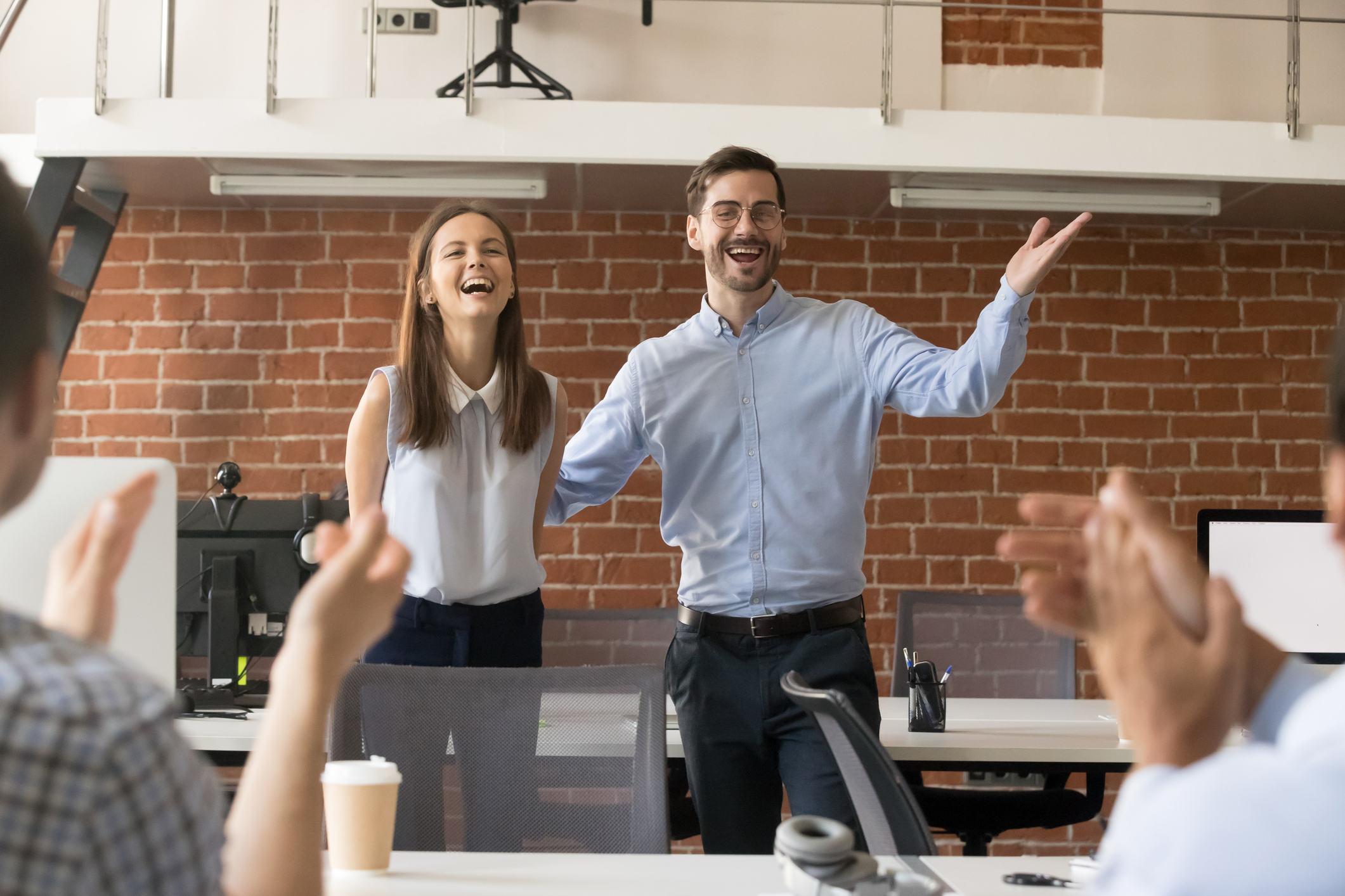 Excited team leader congratulating employee with promotion while team applauding